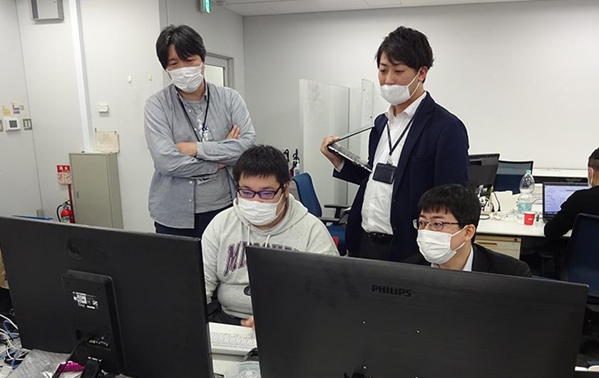 写真 : プロジェクトルームで緊急開発を行う対策チーム