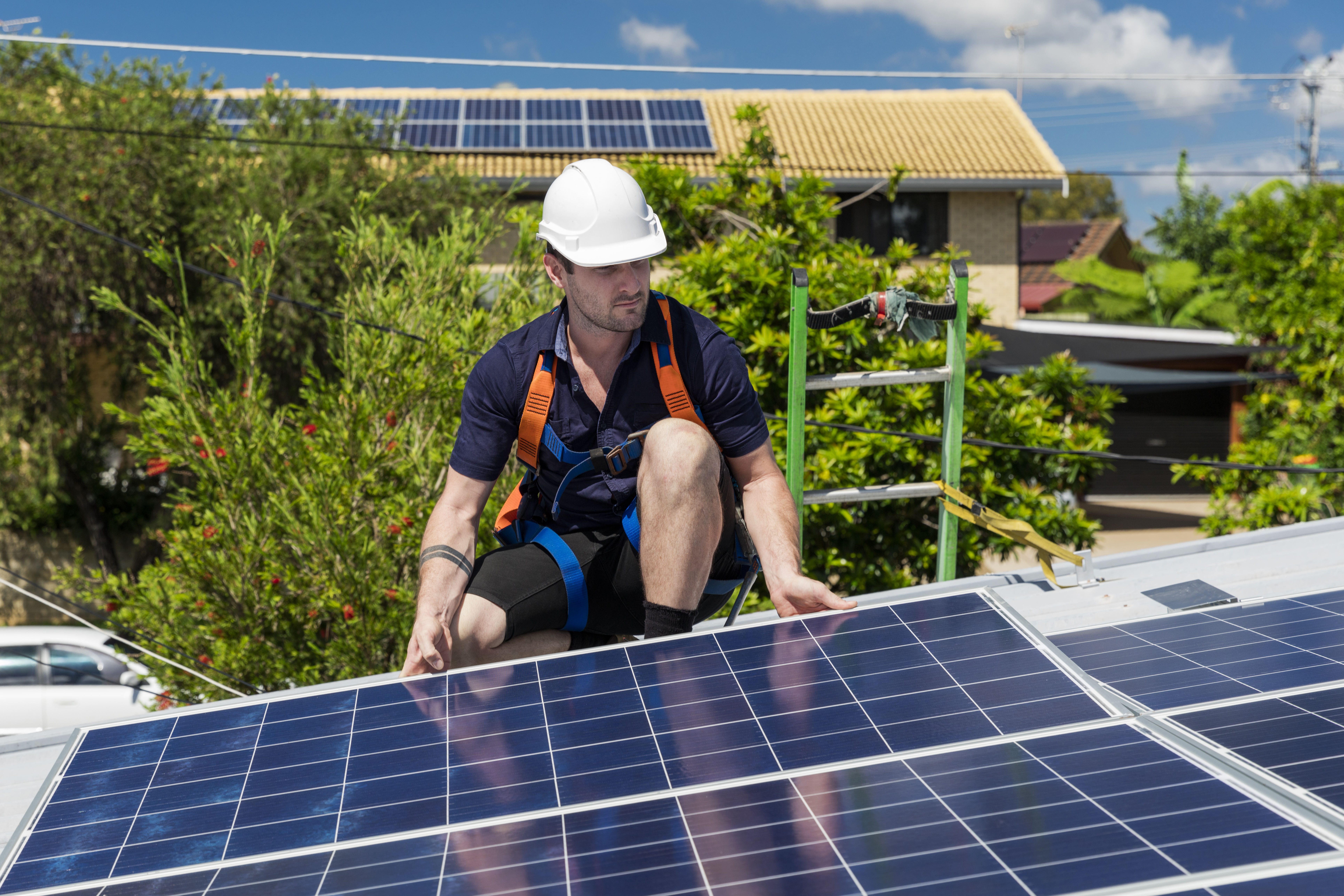 Solar panel technician with drill installing solar panels on roof