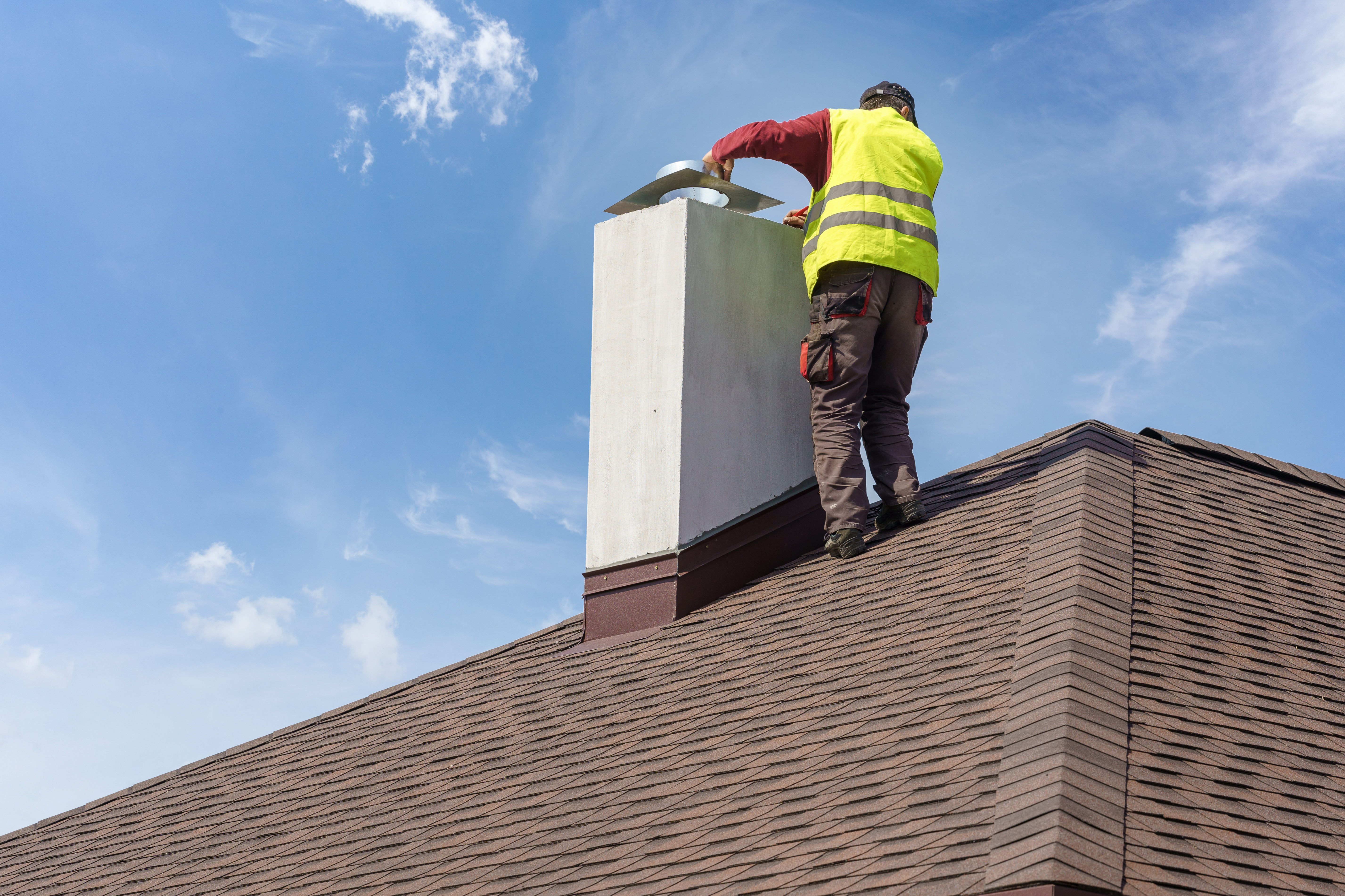 Skilled workman in protective work wear and special uniform install chimney on roof top of new house under construction