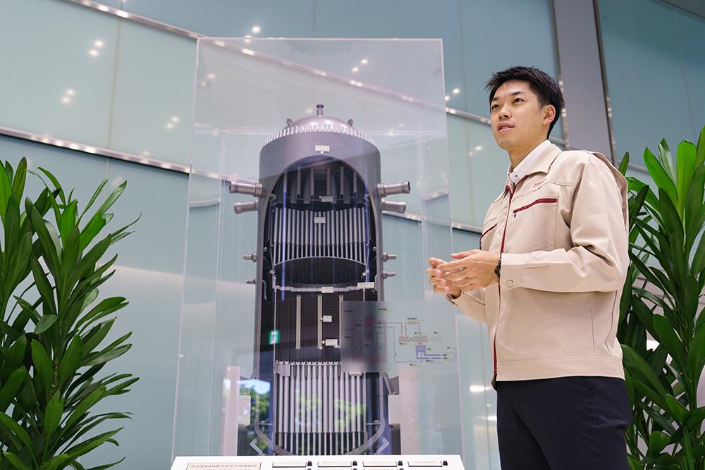 原子炉の模型を使って説明する玉井氏