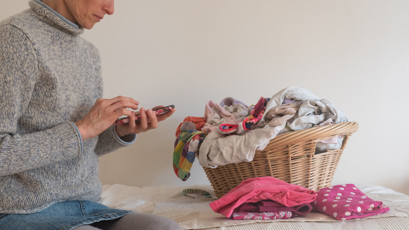 Woman using smart phone while folding laundry