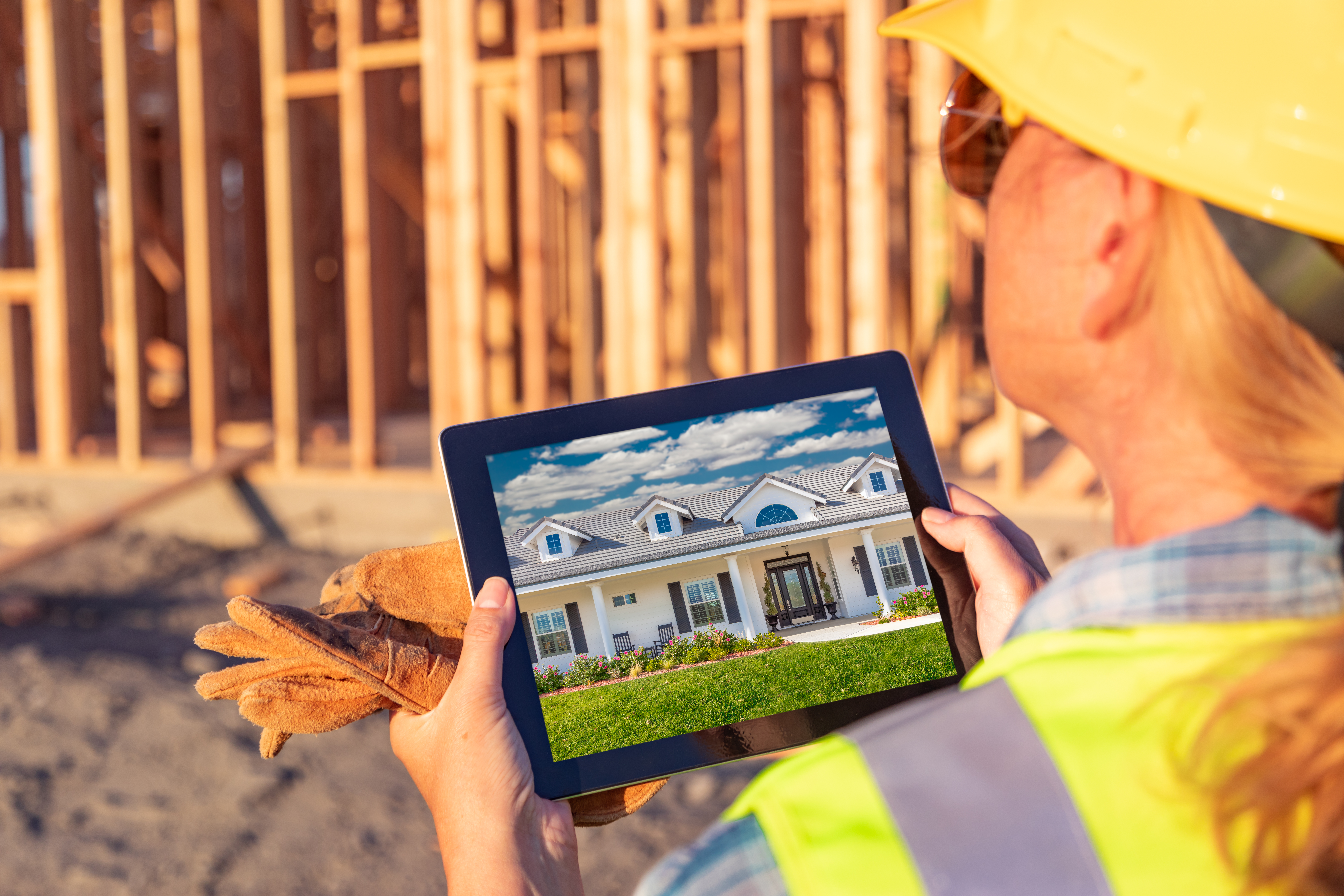Female Construction Worker Reviewing House Photo on Computer Pad at Construction Site