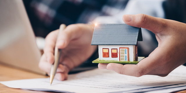 Close up real estate agent with house model hand putting signing contract,have a contract in place to protect it,signing of modest agreements form in office.Concept real estate,moving home or renting property