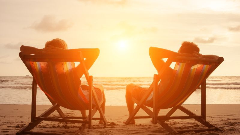 Romantic holiday travel. Silhouette of happy young couple sitting in deck chairs in luxury beach hotel at sunset near the sea. Love and relationship concept. Summer vacation in tropical paradise island.