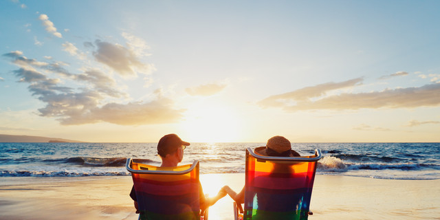 A couple, in beach chairs, holding hands at sunset