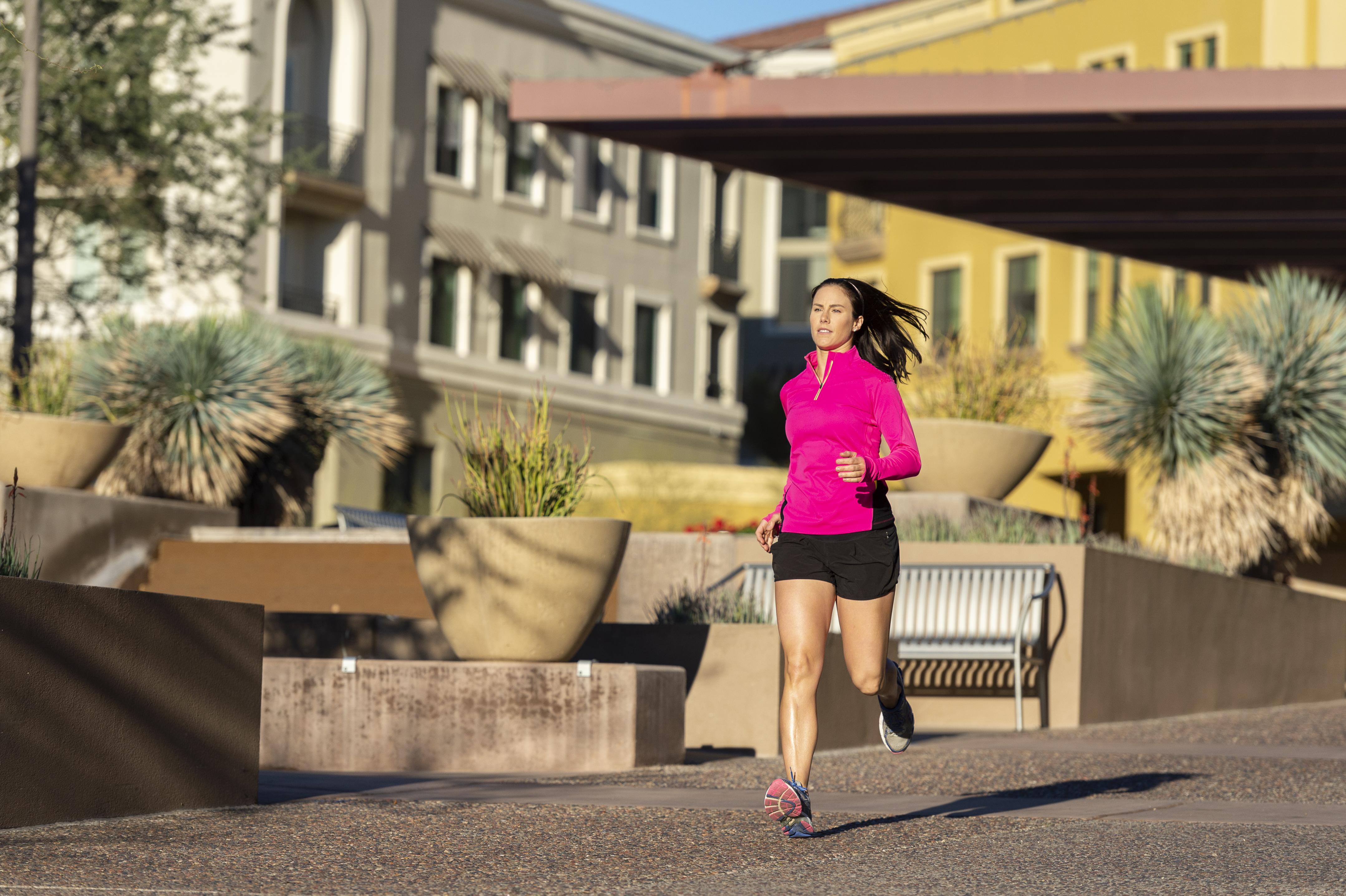 Beautiful Caucasian woman running in town