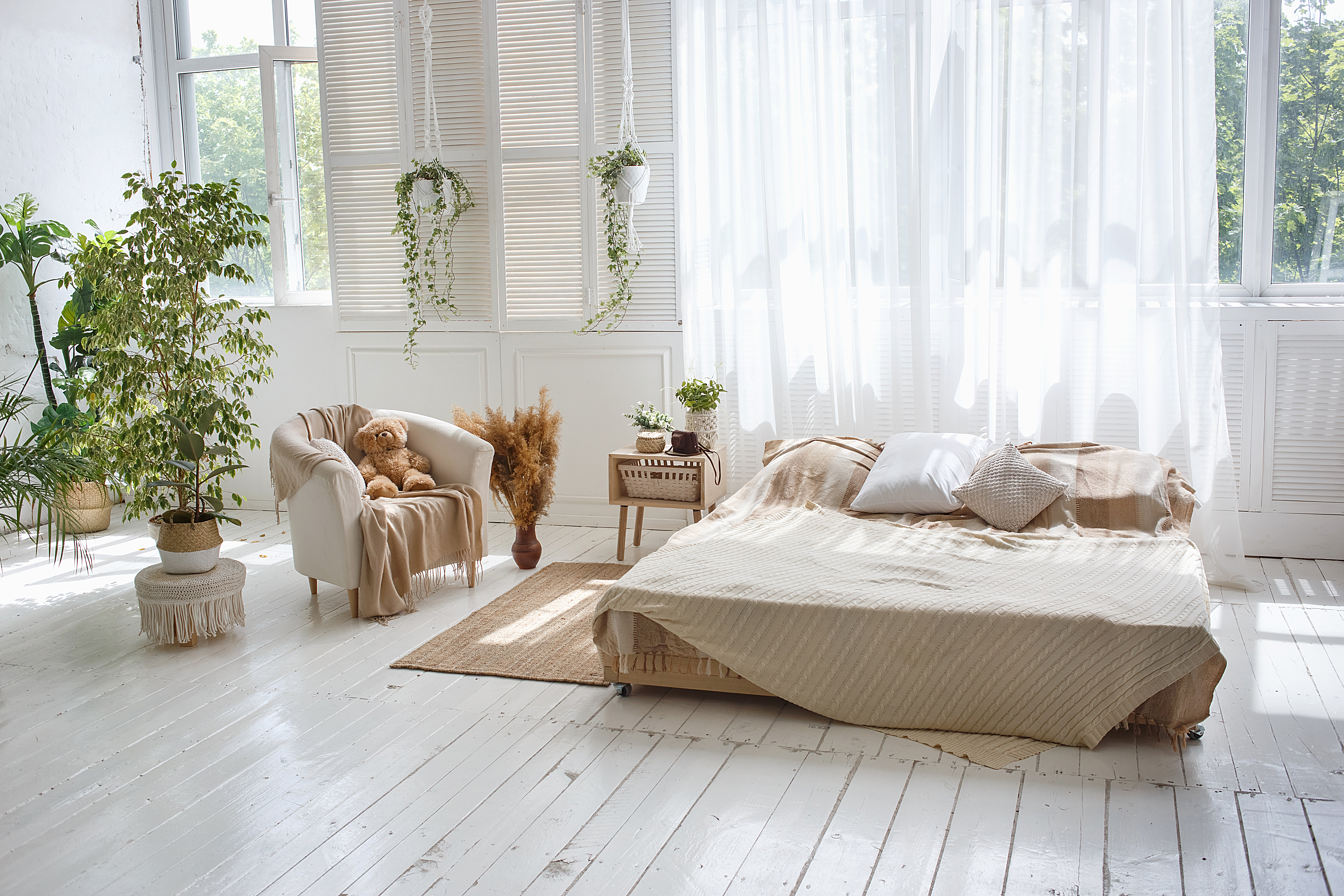 Stylish bright loft cozy room with double bed, armchair, green plants, curtains, white brick walls and wooden floor.