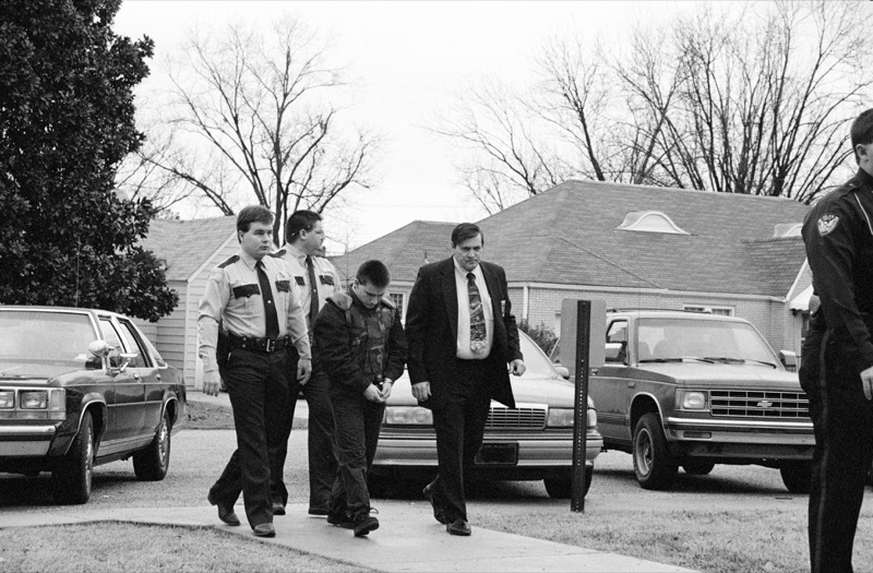 Jessie Misskelley wearing handcuffs being escorted by police officers and a detective