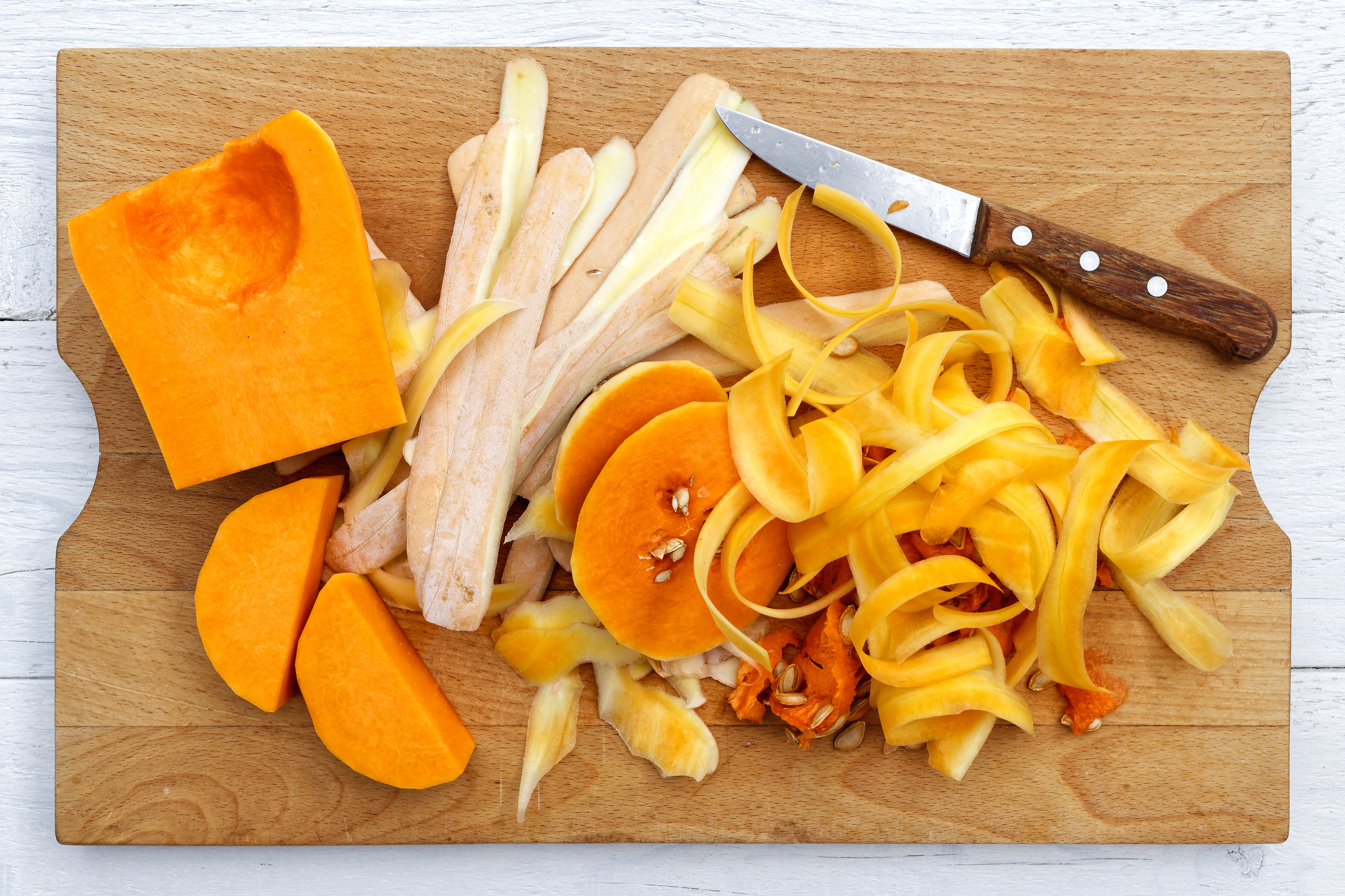 Cut up butternut squash with peels and knife on brown wood chopping board isolated on white from above.