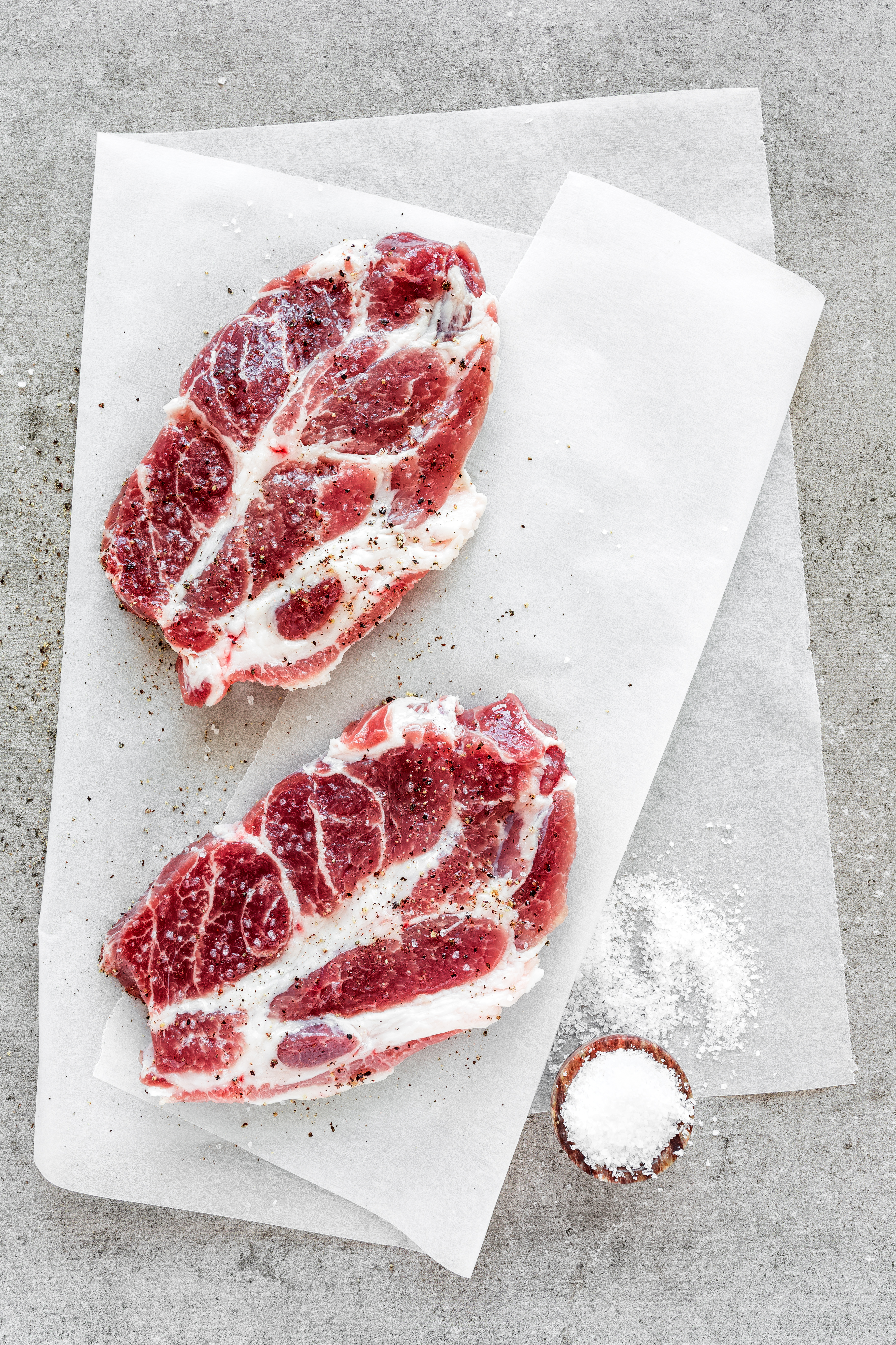Raw meat steaks on stone background, top view