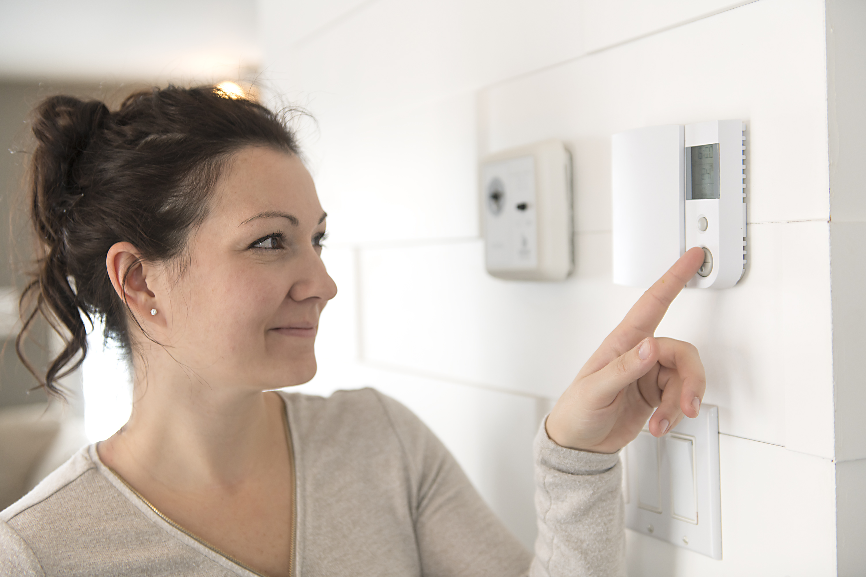 A nice woman set the thermostat at house.