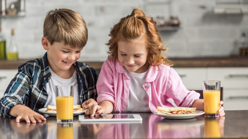 happy little brother and sister using tablet during breakfast at kitchen