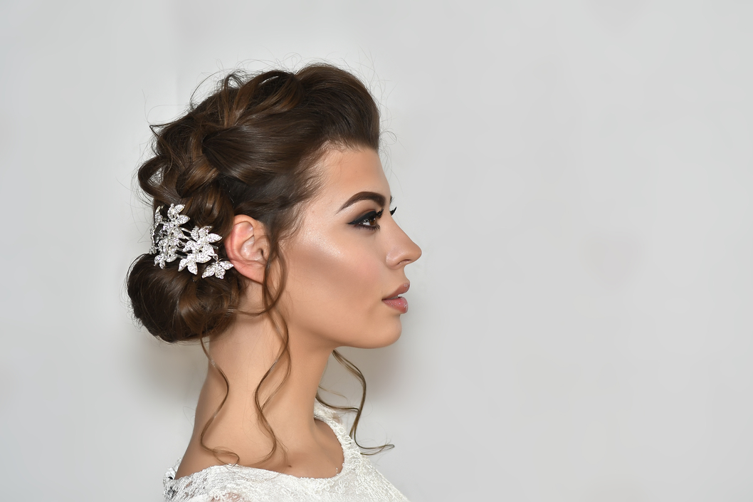 side profile of a woman with a curly updo hairstyle and sparkly accessory.jpg