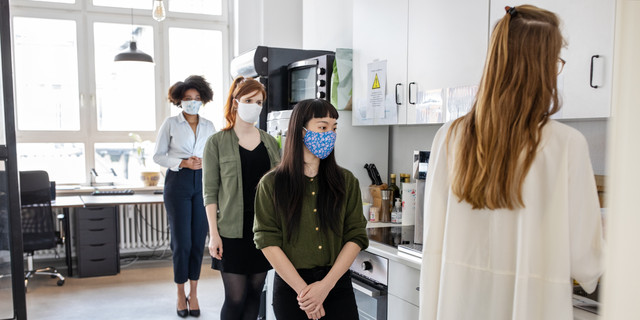 Businesswomen maintaining social distancing in office cafeteria