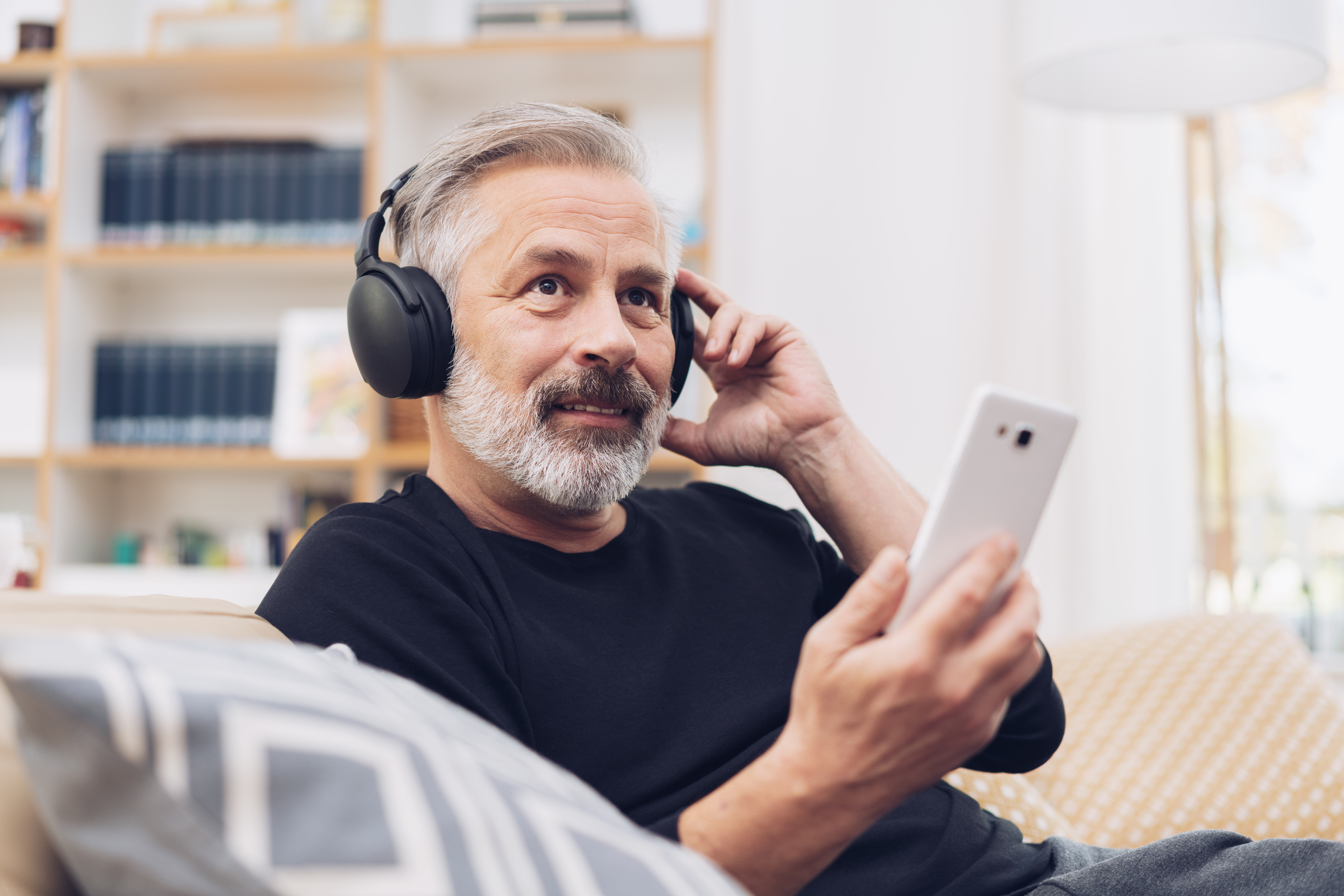 Middle-aged man listening to music online at home