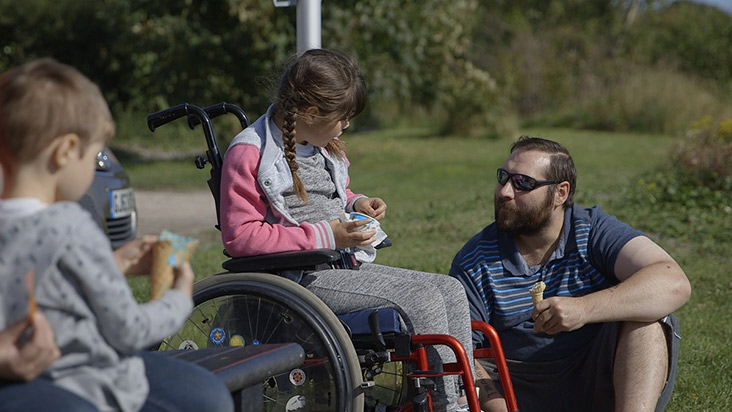 Father assisting disabled daughter