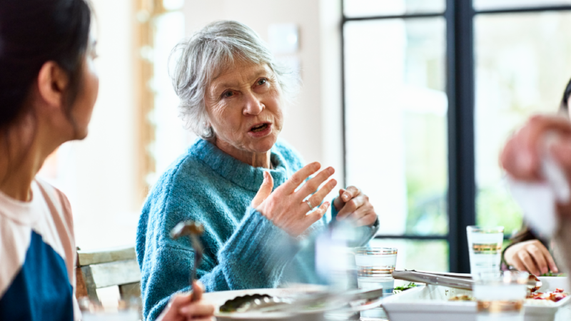 Senior woman talking and gesturing at dinner party