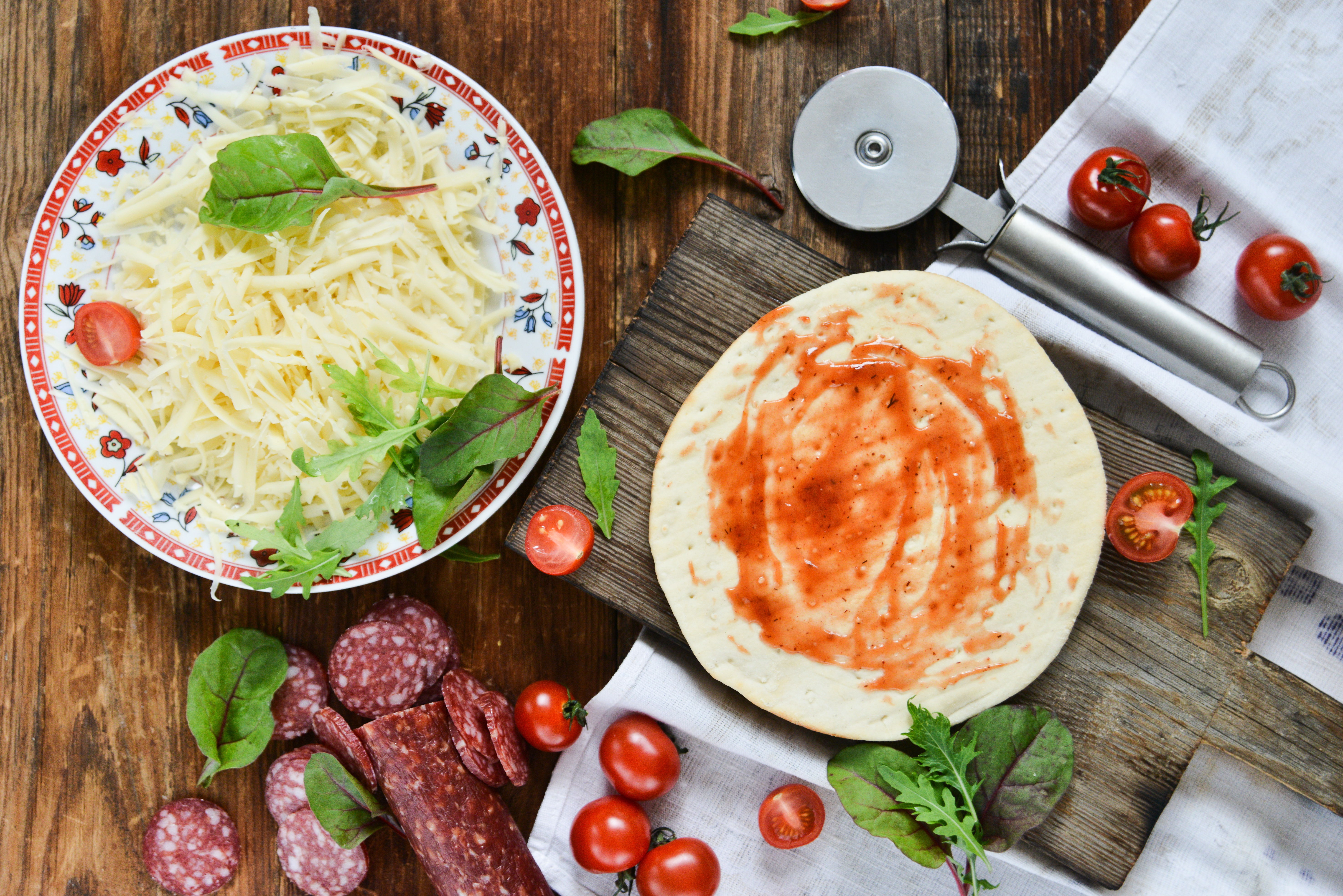 Ingredients for Pizza: basis dough, salami sausage, cherry tomatoes, grated cheese, tomato paste, herbs and arugula. Natural Wooden Background With Linen Napkin and Knife For Pizza