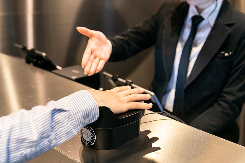写真 : 受付カウンターに設けられた認証端末。右手のひらをかざすだけで、IDを確認することなく入場できる