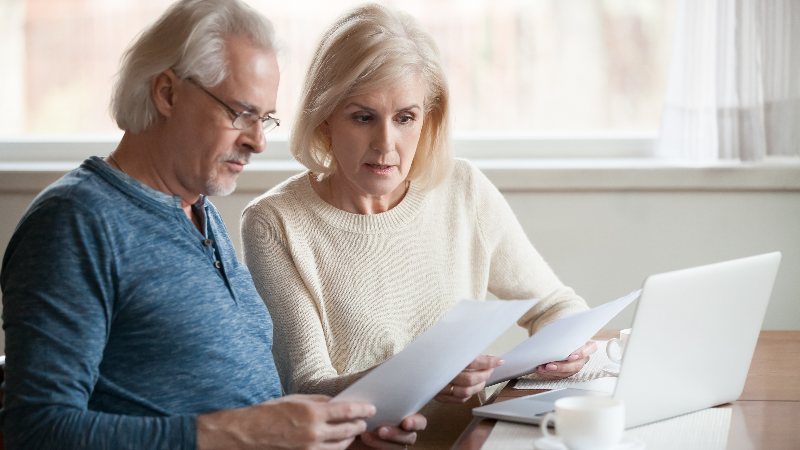 Serious worried senior couple reading documents calculating bills to pay