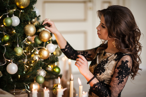 a woman with wavy hair putting decorations on a christmas tree.jpg
