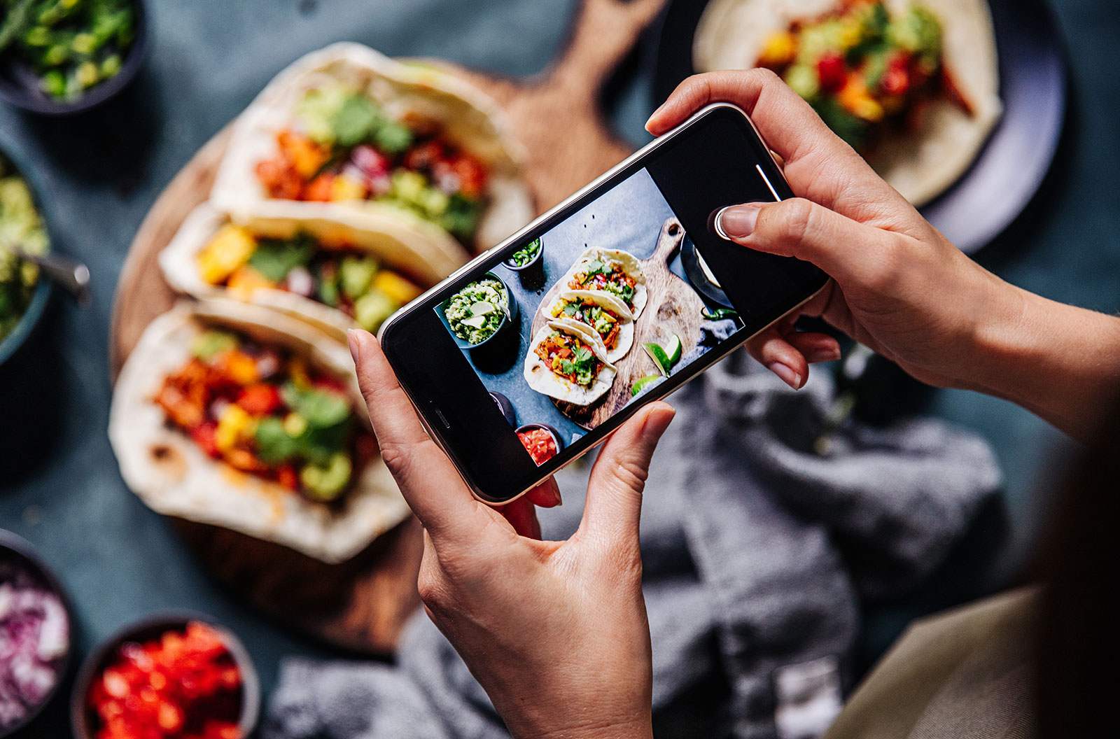 Hand of a person taking photograph of tacos on table with a mobile phone