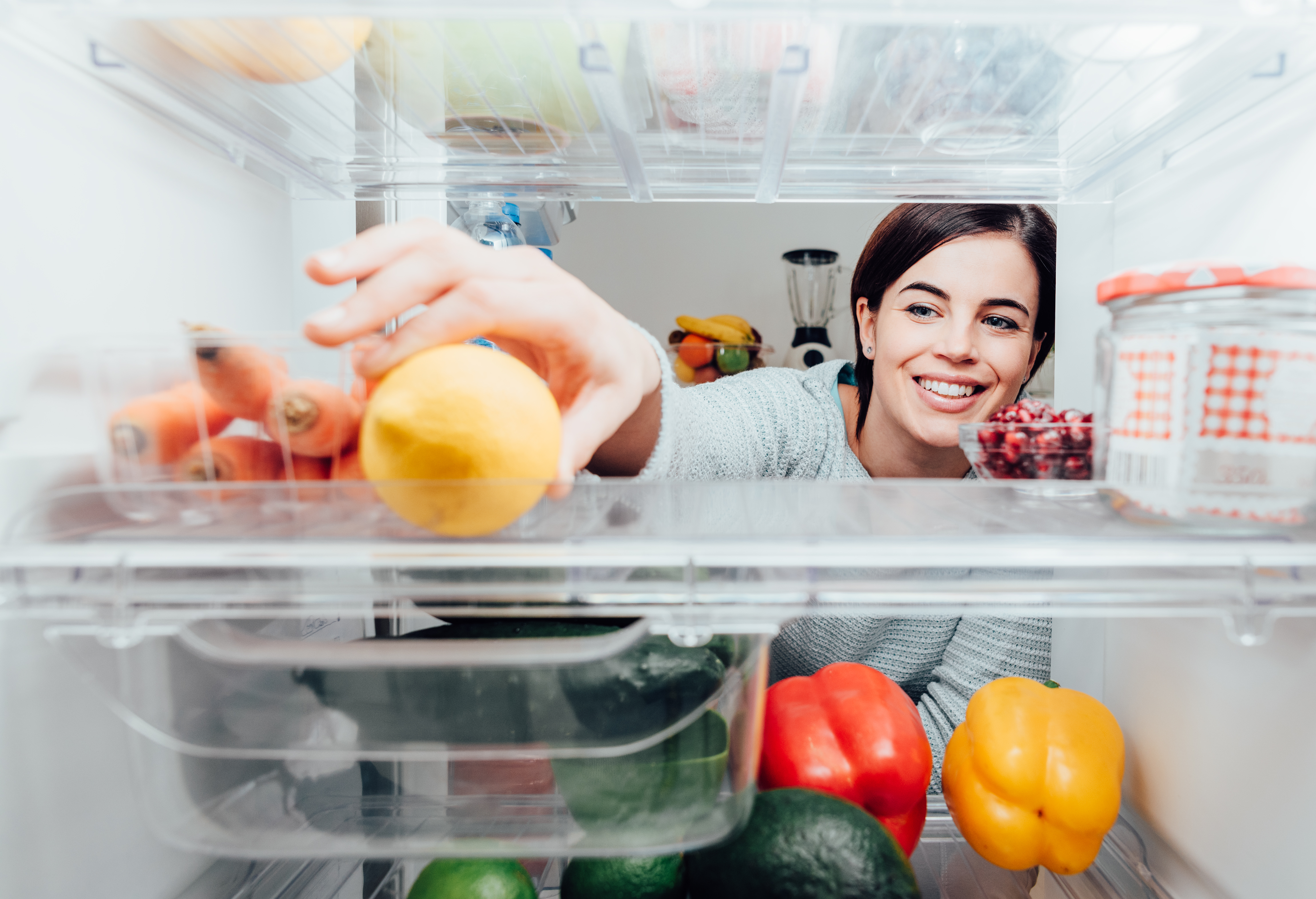 Woman taking a lemon out of the fridge