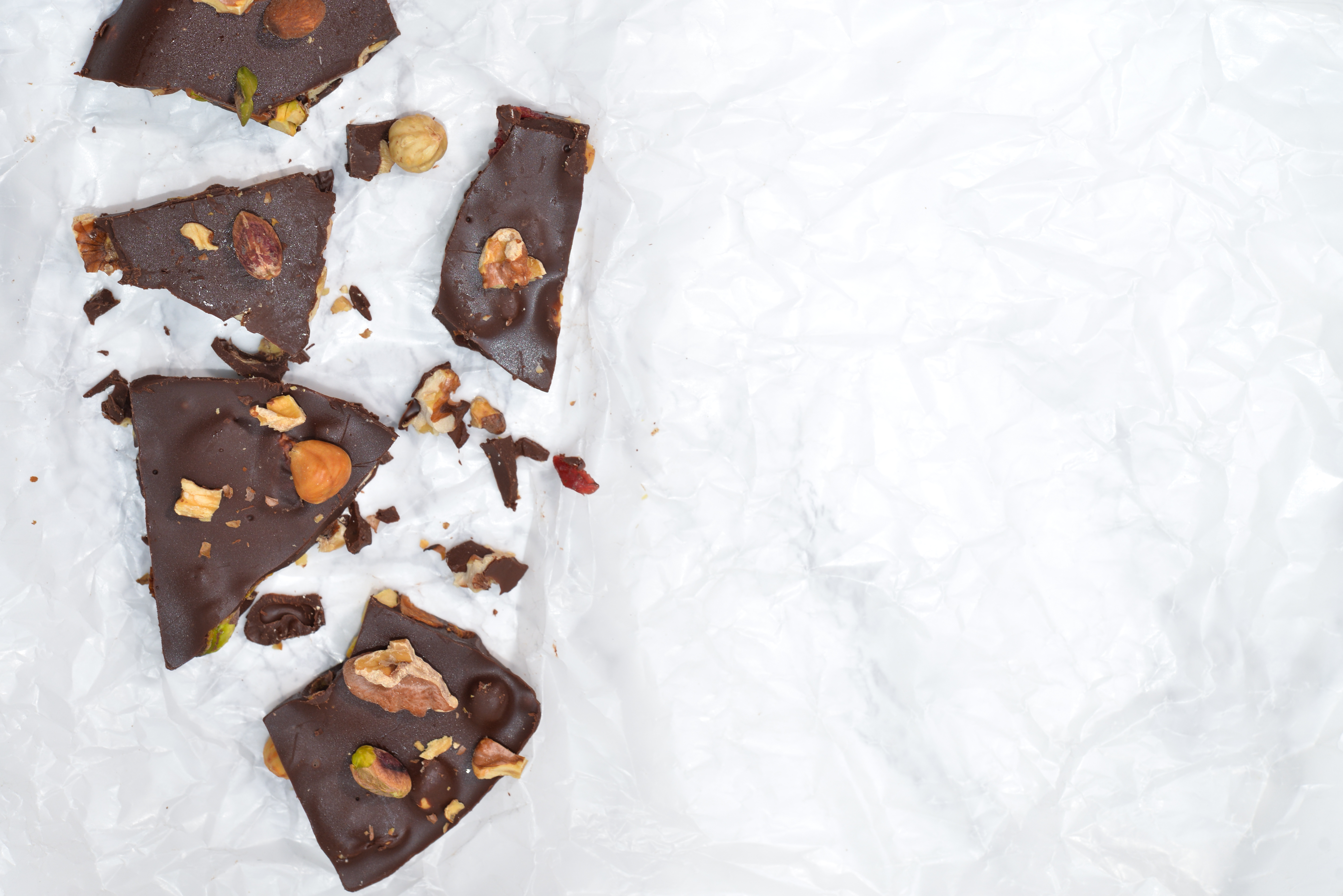 Dark chocolate bark with mixed nuts on wax paper