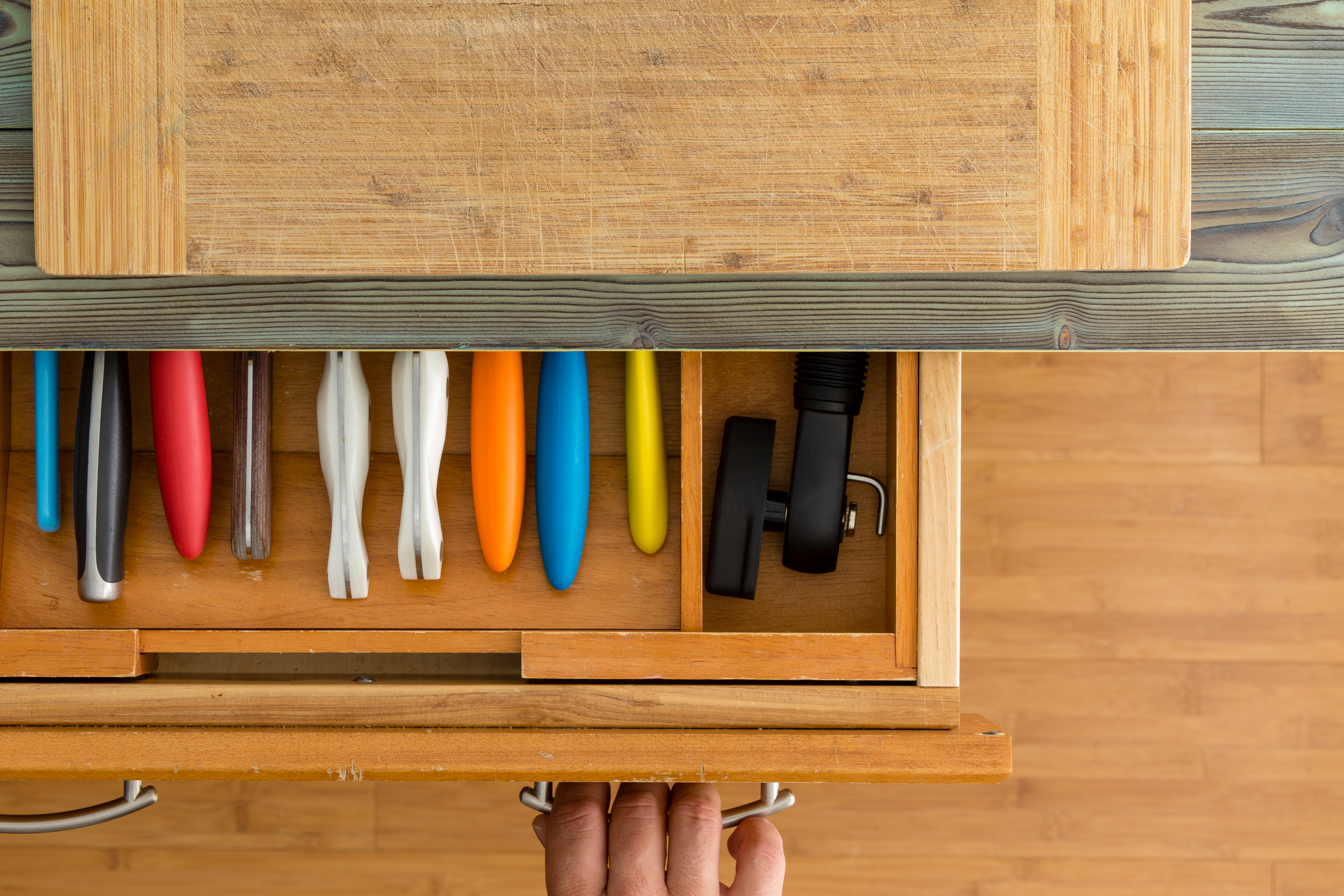 Man or chef opening a knife drawer in a kitchen