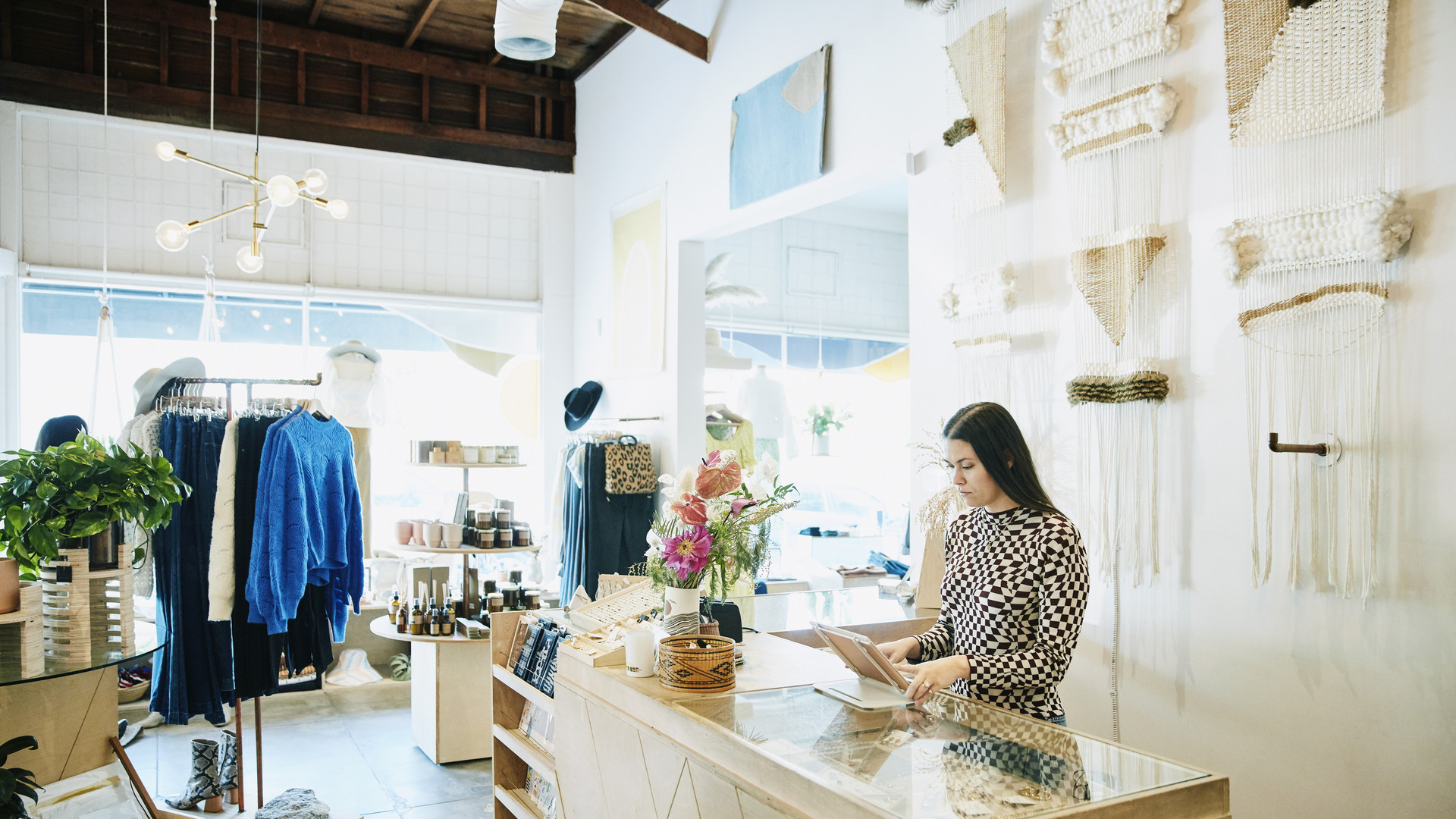 Shop owner working on digital tablet behind counter in clothing boutique