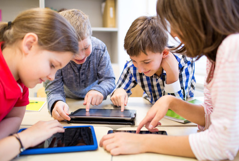 group of school kids with tablet device in classroom