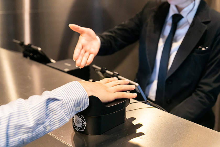 Photo : An authentication device at the reception counter. Audience members can enter the building merely by placing the palm of his or her right hand over the device without showing ID.