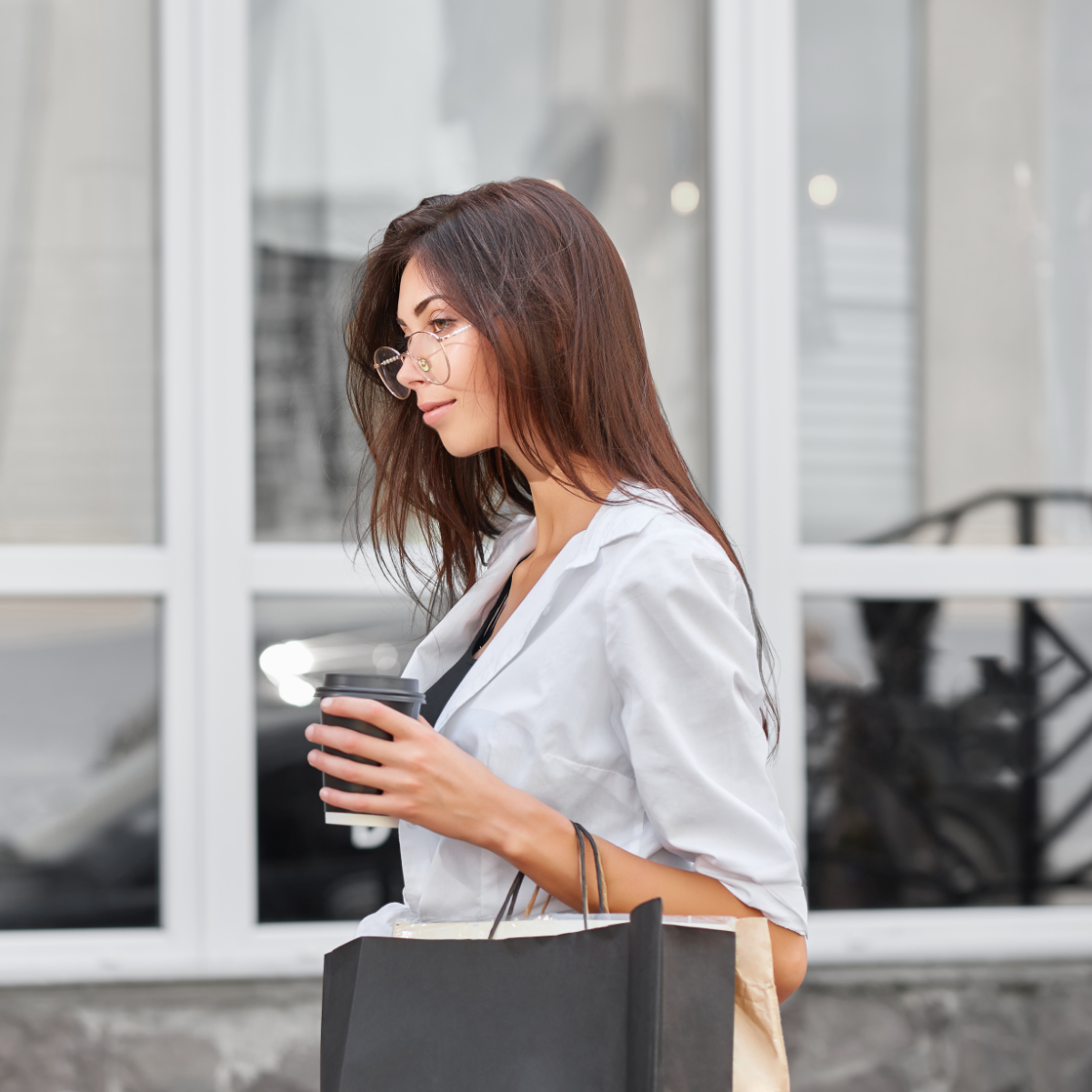 Young slim girl with long brunette hair going out from shop carrying bags.