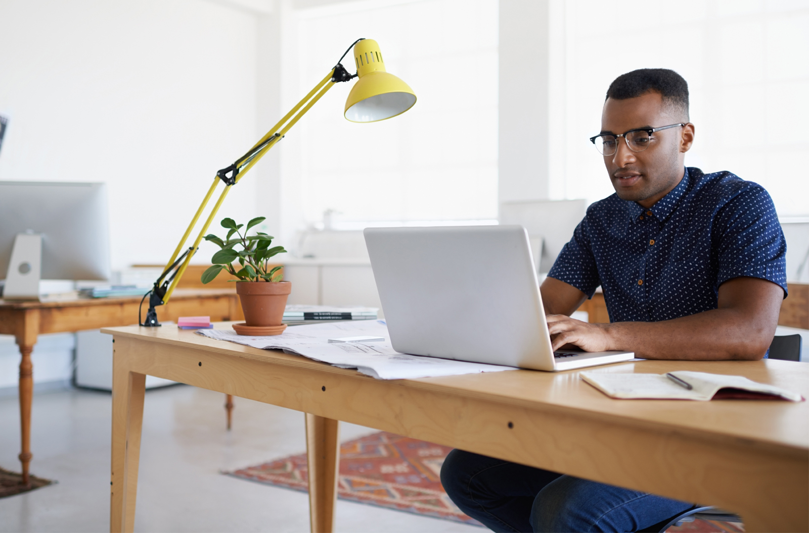 Young man working at his desk typing on a laptop computer