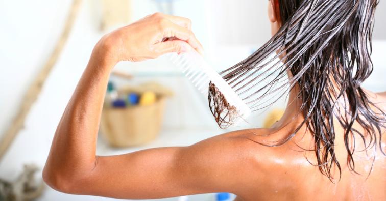 femme dans sa salle de bain peignant ses cheveux