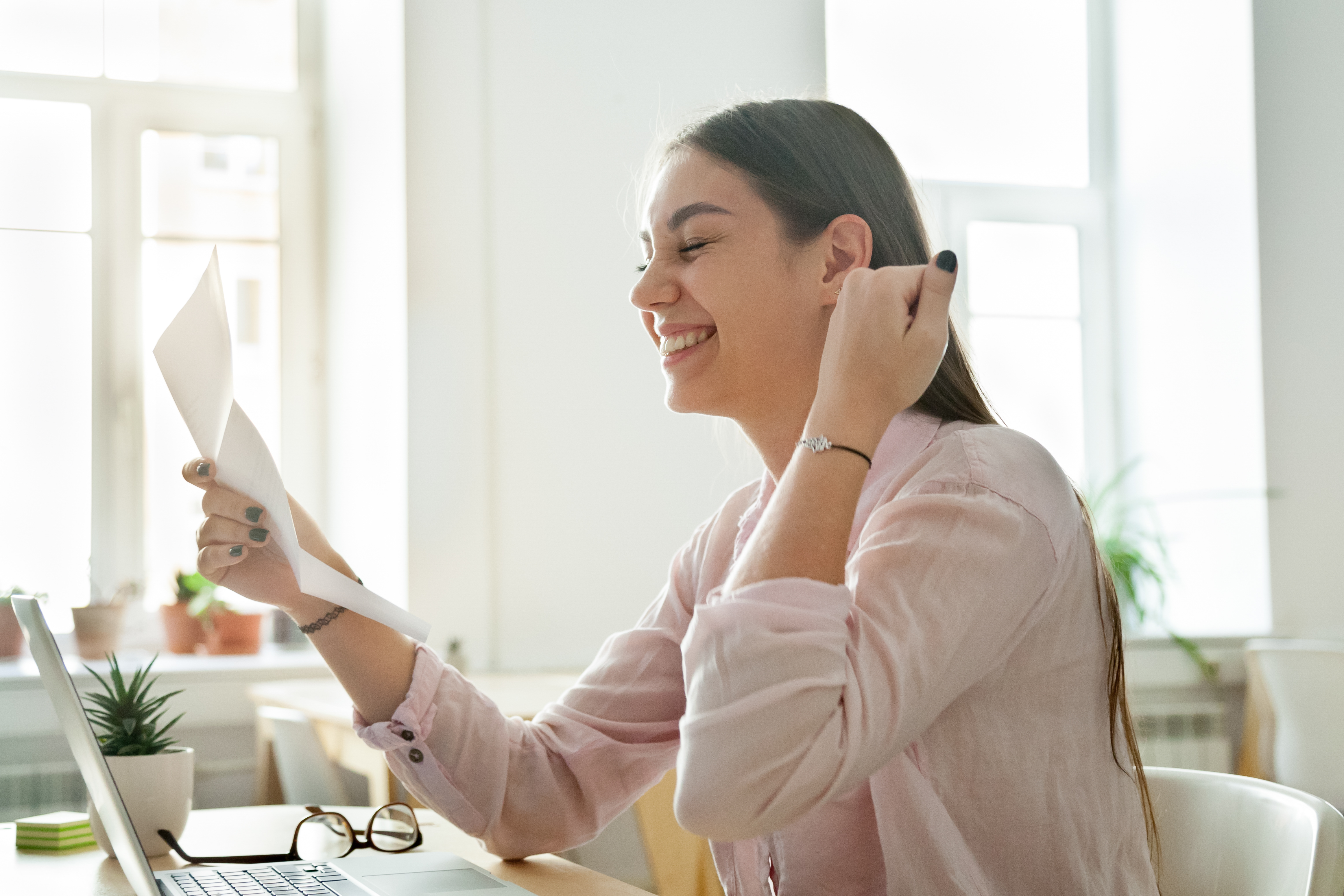 Happy female employee excited reading promotion letter