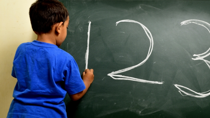 four year old Indian boy writing 123 on chalk board