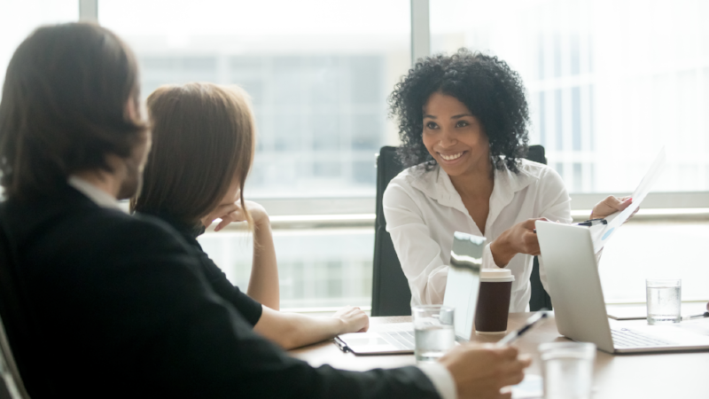 Smiling african american businesswoman discussing business document with caucasian partners