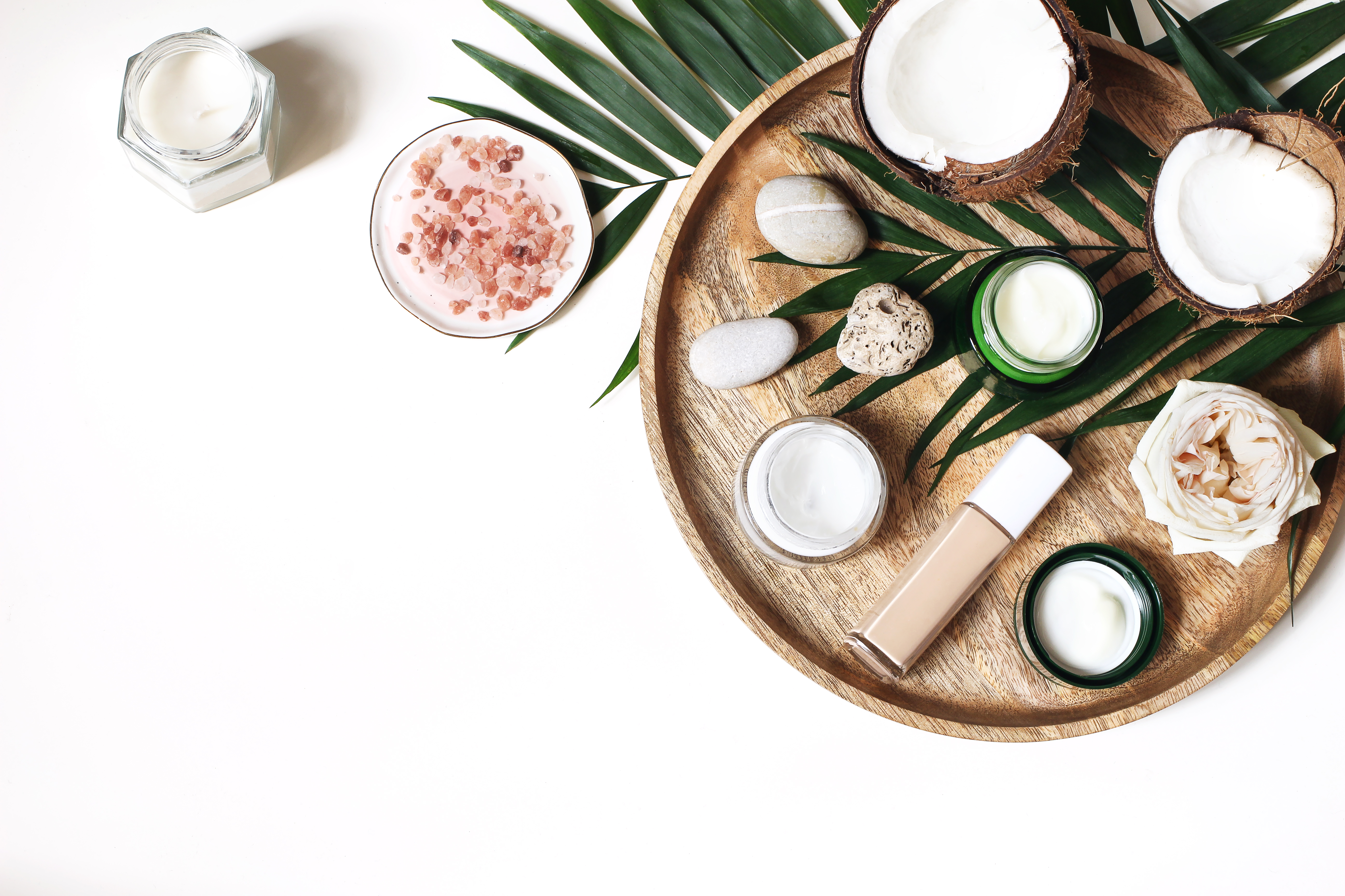 Styled beauty composition. Skin creams, makeup bottle, rose and pebble stones on wooden tray. Coconuts, tropical palm leaves decoration. Cosmetics, spa concept. Empty space, flat lay, top view.
