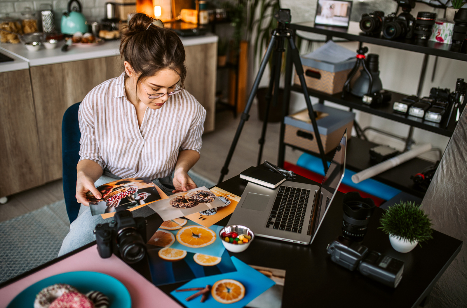 Female photographer sitting at her kitchen table reviewing and selecting images of food