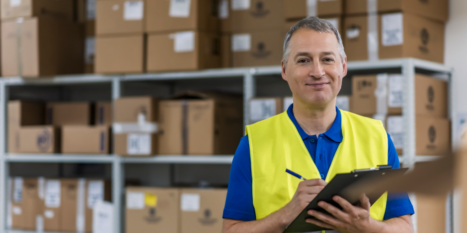 Warehouse worker holding clipboard in a large warehouse