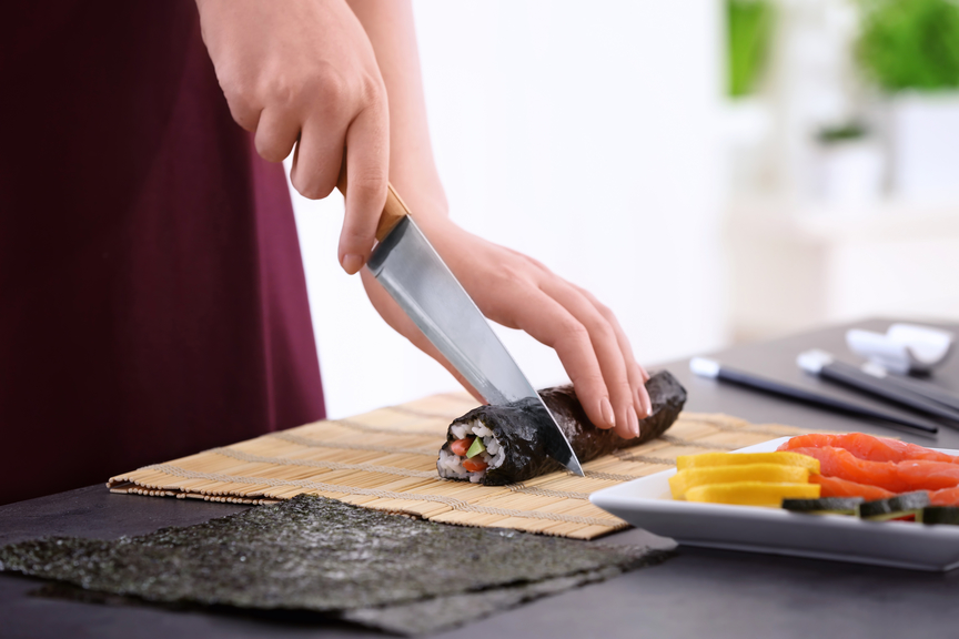 Cutting a maki roll on a sushi mat