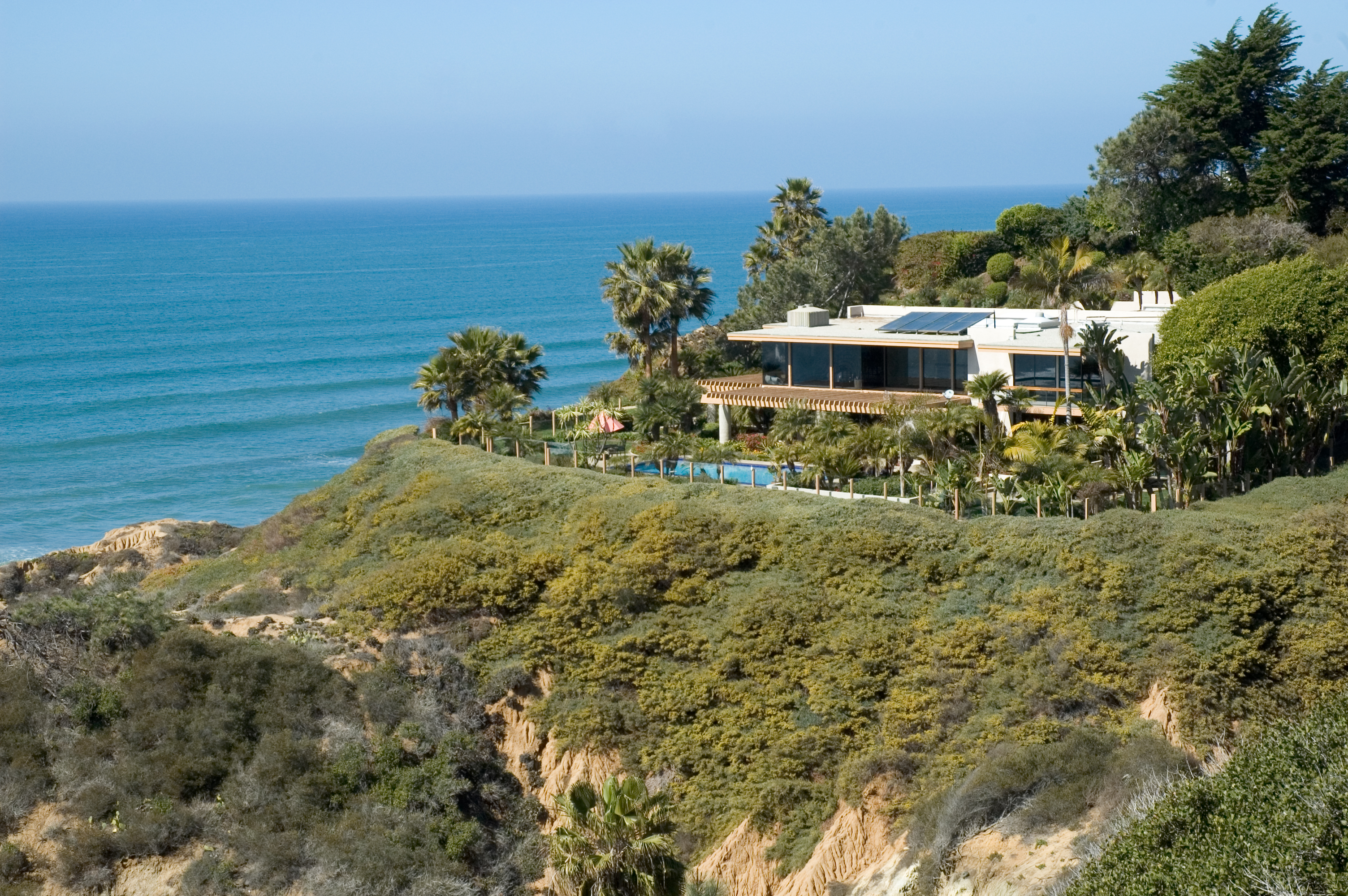Beach house on top of cliff with sea in background