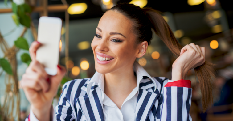 Gorgeous stylish young girl is making a selfie in a cafe while holding her ponytail.