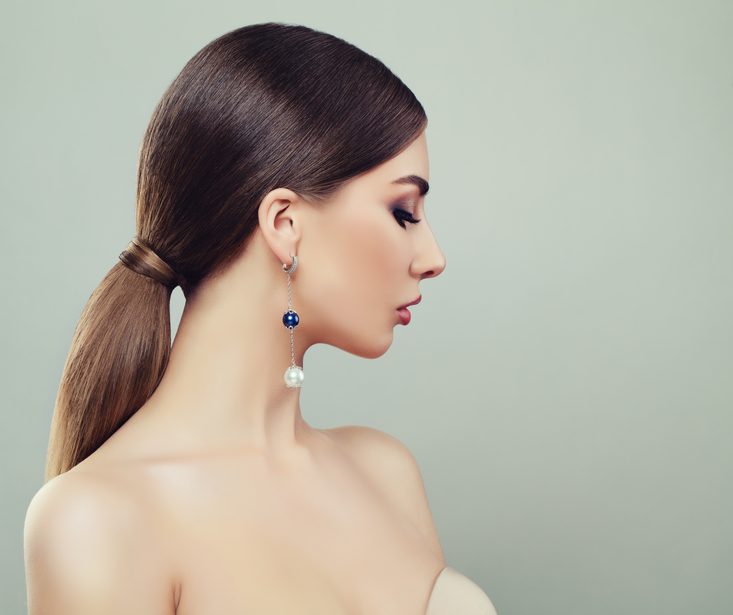 side profile of a woman with a low brown ponytail, wearing earrings.jpg