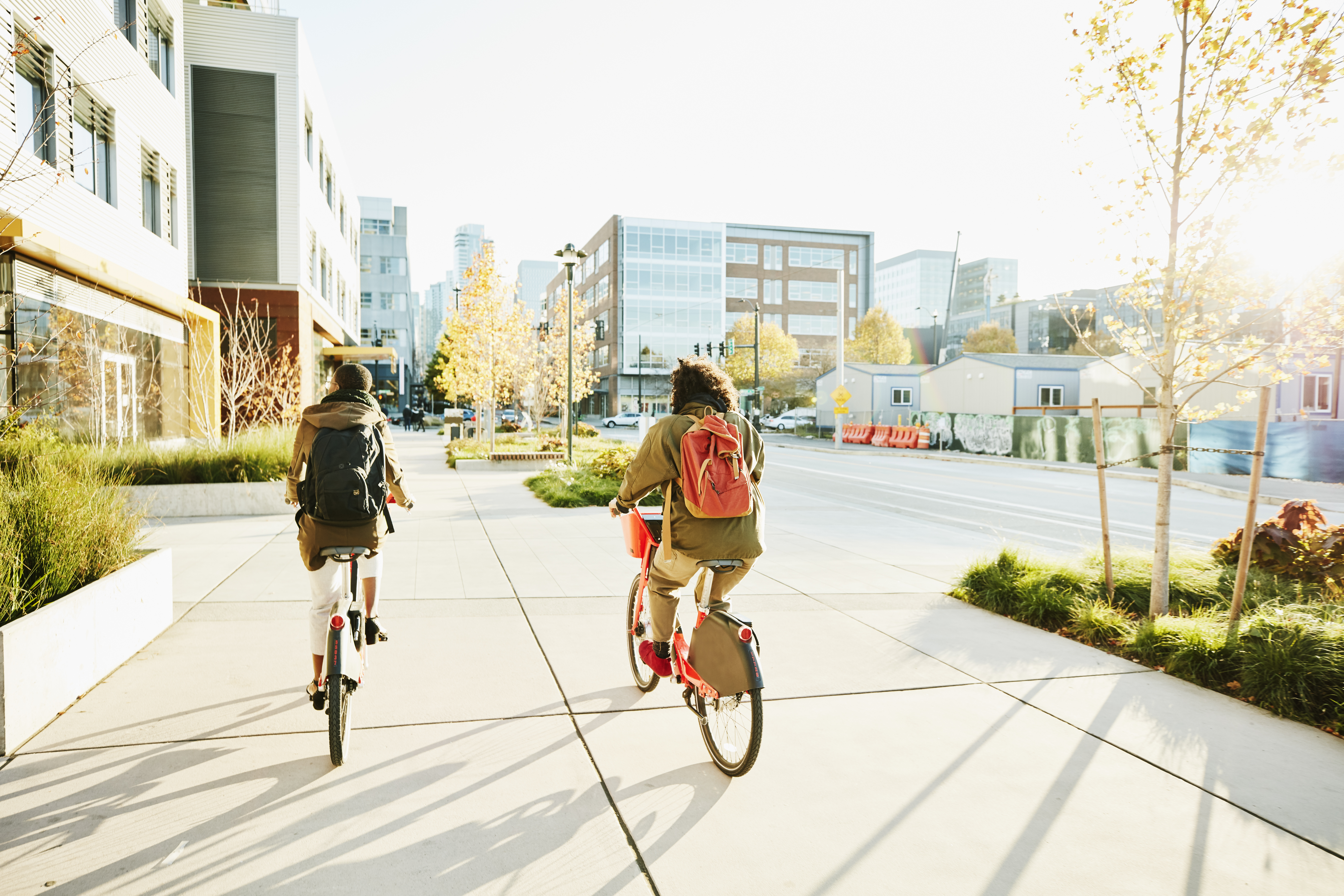Rear view of friends commuting to work on electric bike share bikes