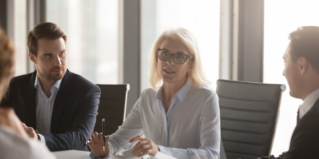 Serious middle aged businesswoman talks at group board executive meeting