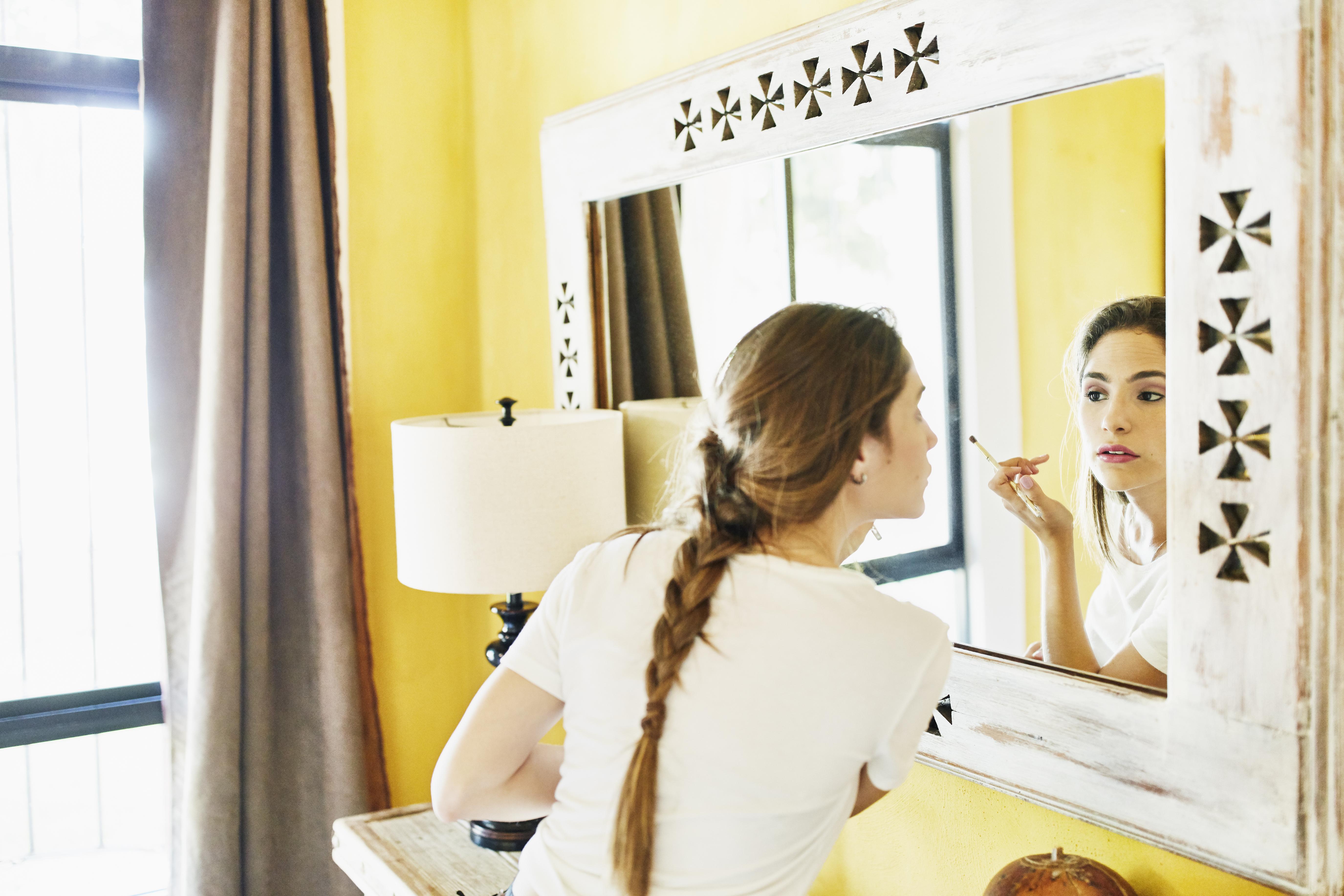 Bride looking in mirror and applying makeup in hotel room before wedding ceremony