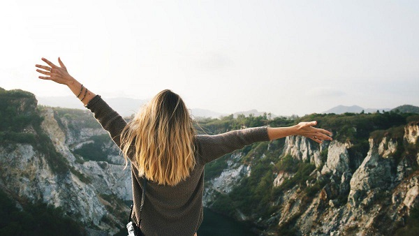 Woman with outstretched arms overlooking a mountain cliff