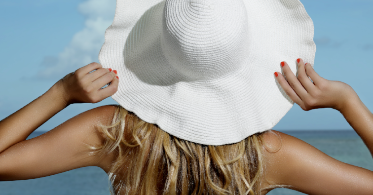 Natural blonde girl smiling wearing an hat on the beach